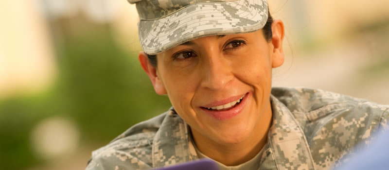 Female military student looking up from laptop